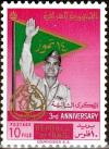 Colnect-1954-965-General-Kassem-in-front-of-flag.jpg